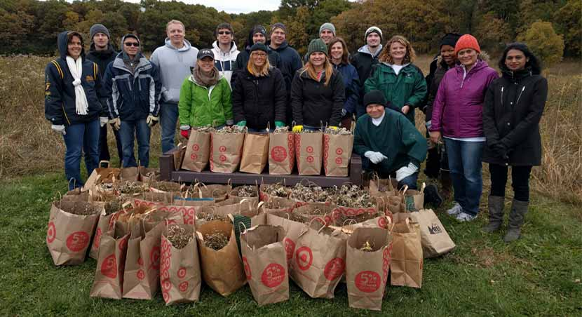 volunteer seed collectors posing for a picture with bags of collected seeds.