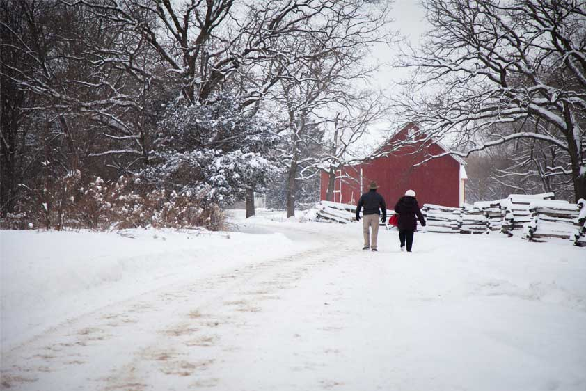 Two people walk toward a historic red barn in the winter at The Landing.